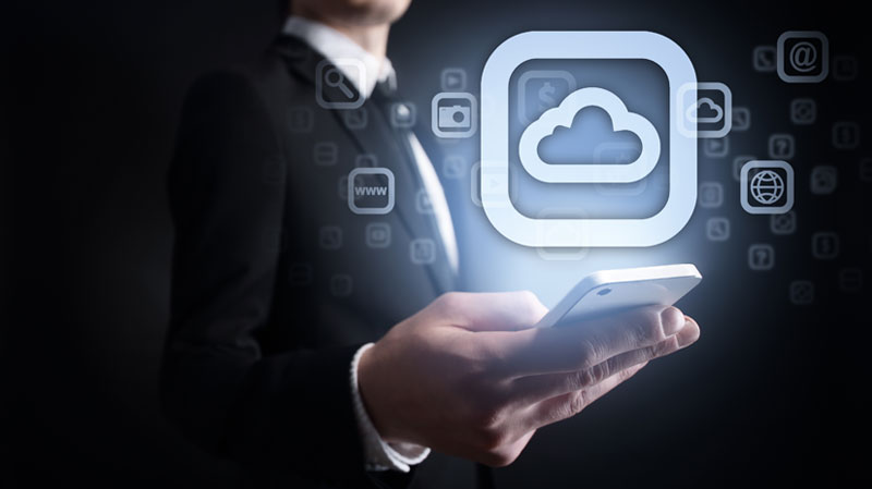 "Business person holding illuminated cell phone with ""cloud"" icon hovering above it"