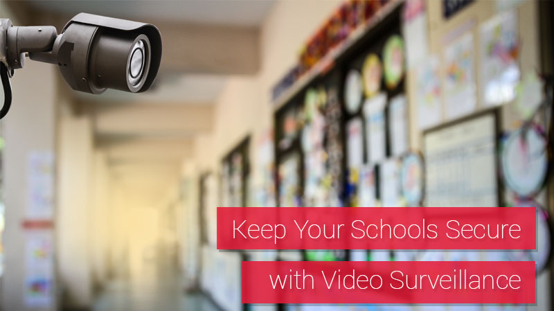 Security camera mounted in a school near a bulletin board displaying a variety of student projects.