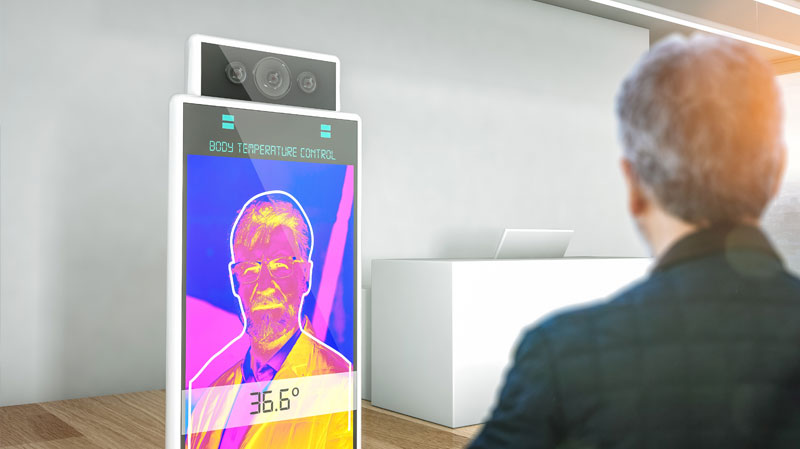 Man standing in front of temperature scanning kiosk in office building.