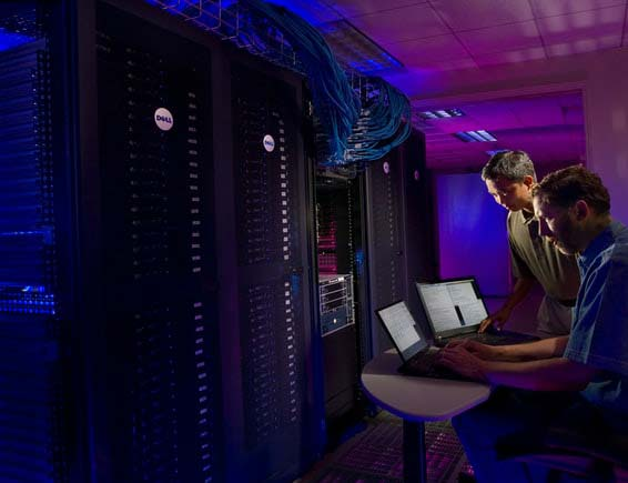 Two men using laptops in front of several full server racks filled with data servers and networking equipment